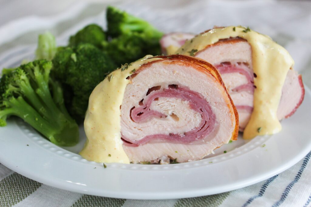 An easy and tasty family dinner, Bacon Wrapped Chicken Cordon Bleu. Chicken breast is rolled up with ham, swiss cheese, and covered in bacon for the juiciest, tastiest chicken cordon bleu served with a homemade, ketogenic honey dijon cream sauce.