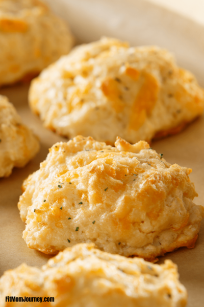 Super easy Keto Cheddar Biscuits that are fluffy and a copycat recipe to a popular restaurant chain.  Garlicy, butter, and delicious, these biscuits are the perfect simple side.