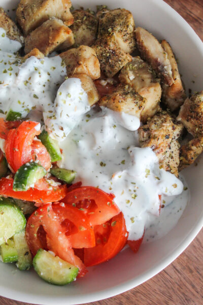 Low Carb Greek Chicken Bowls packed with everyone's favorite greek flavors!  Delicious in a bowl with cucumber and tomato salad, onions, homemade tzatziki, and feta cheese.