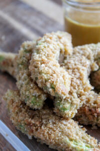 Fresh avocado slices coated in crispy pork rind breadcrumbs and baked until crispy and delicious.  These Crispy Keto Avocado fries are easy to make and sure to impress.