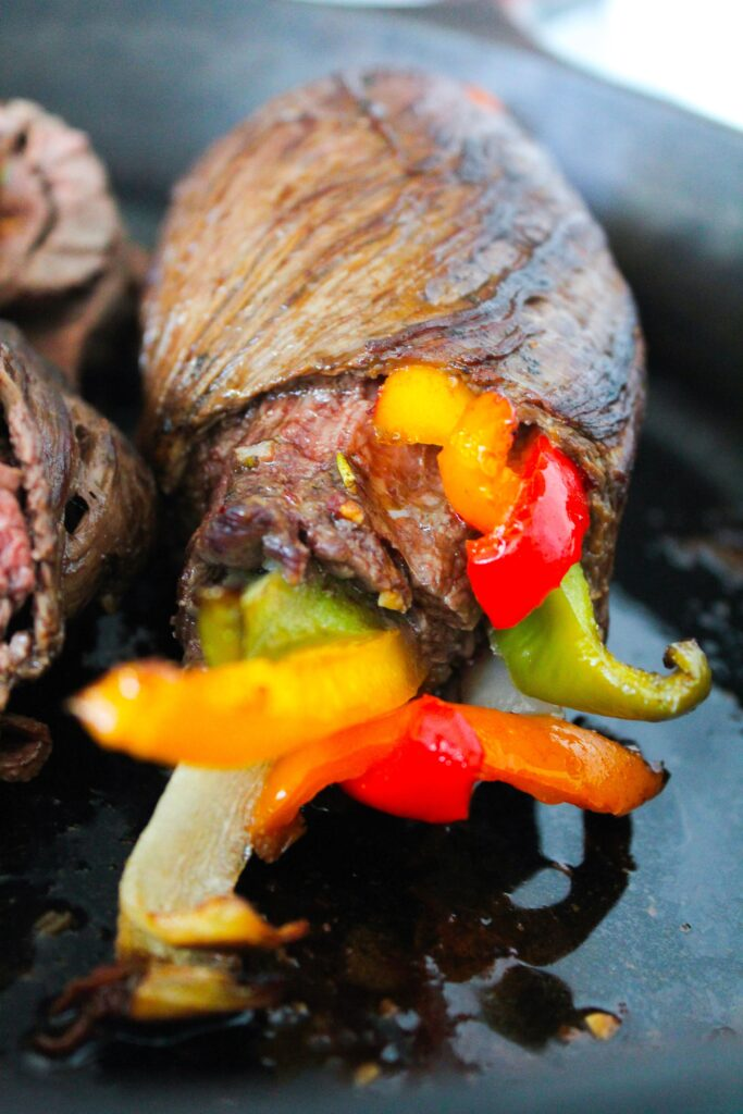 Flank Steak marinated then stuffed with bell peppers and onions. Marinate, roll, and bake, then finish in the oven for a delicious dinner!